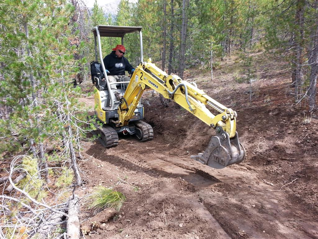 Rob Giustina with Progressive Trail Design shaping tread and cutting backslope in a mini-excavator